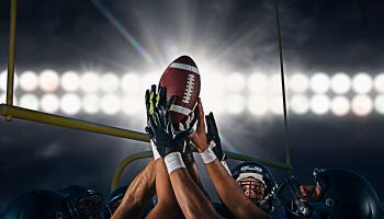 Victorious teenage and young male american football team holding up ball at night