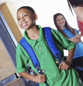 Pround young boy walking into school with students