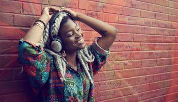 Black woman leaning on brick wall listening to headphones