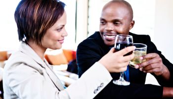 Smiling couple celebrating with cocktails clink glasses