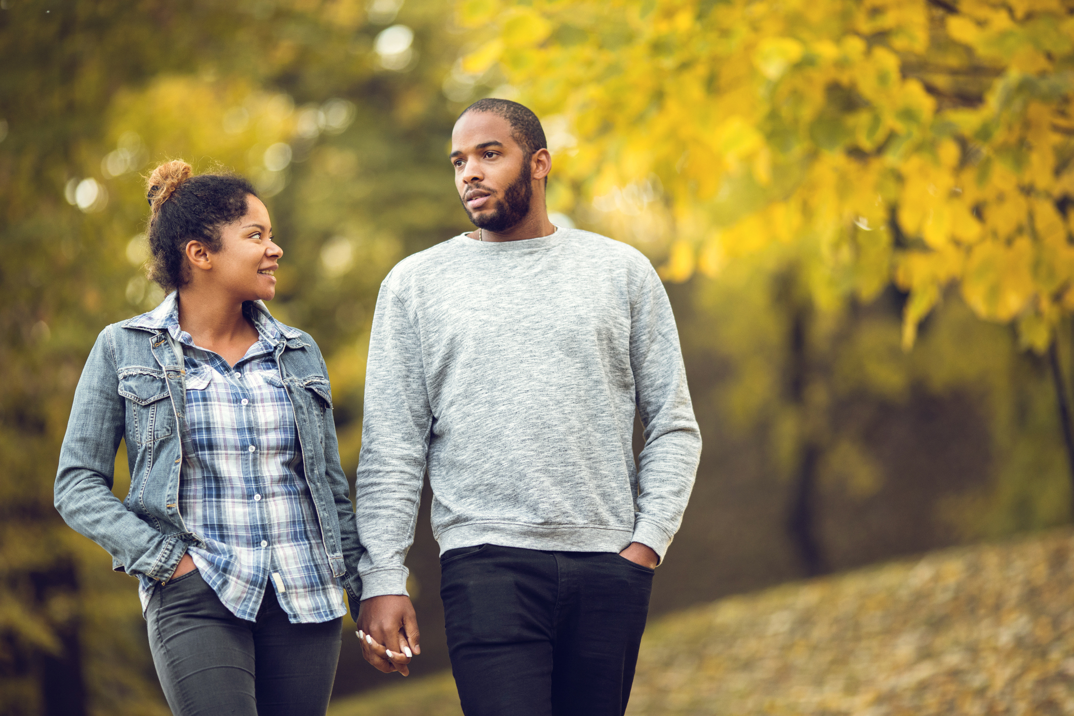 Young black couple holding hands and taking a walk in autumn day.