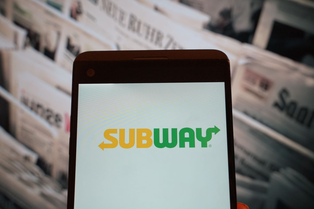 The logo of Subway is seen on a smartphone...