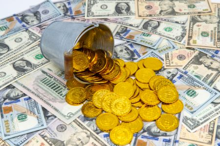 gold coins pouring out of the basket on dollar background