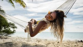 Happy woman relaxing in hammock on the beach.