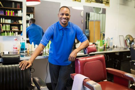 Black barber smiling in retro barbershop