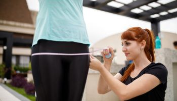 Personal trainer taking measurement of her client's hip